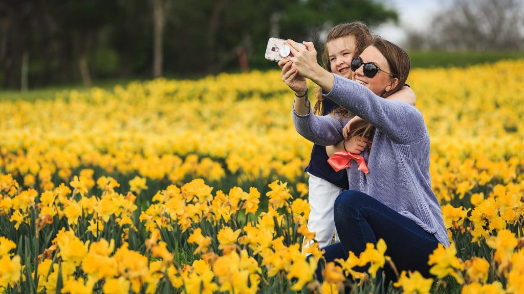 Girl and mum taking selfie in field of yellow daffodils symbolising rebirth and new beginnings