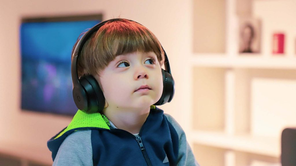 Boy with disability listening with earphones in class