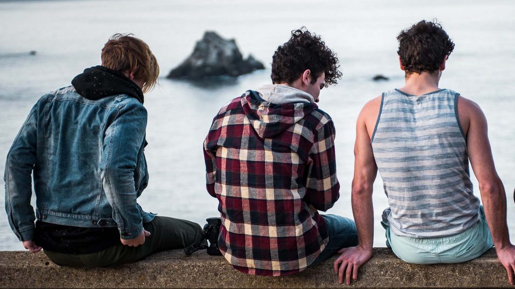 Teenage boys chatting on a wall overlooking beach improving mental and emotional health