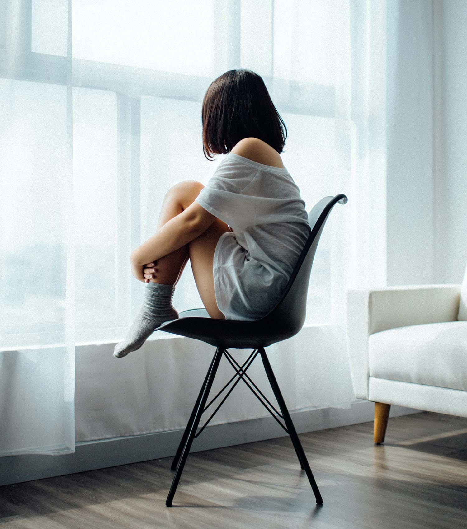 Girl with anxiety and sadness holding legs sitting on chair alone gazing out the window