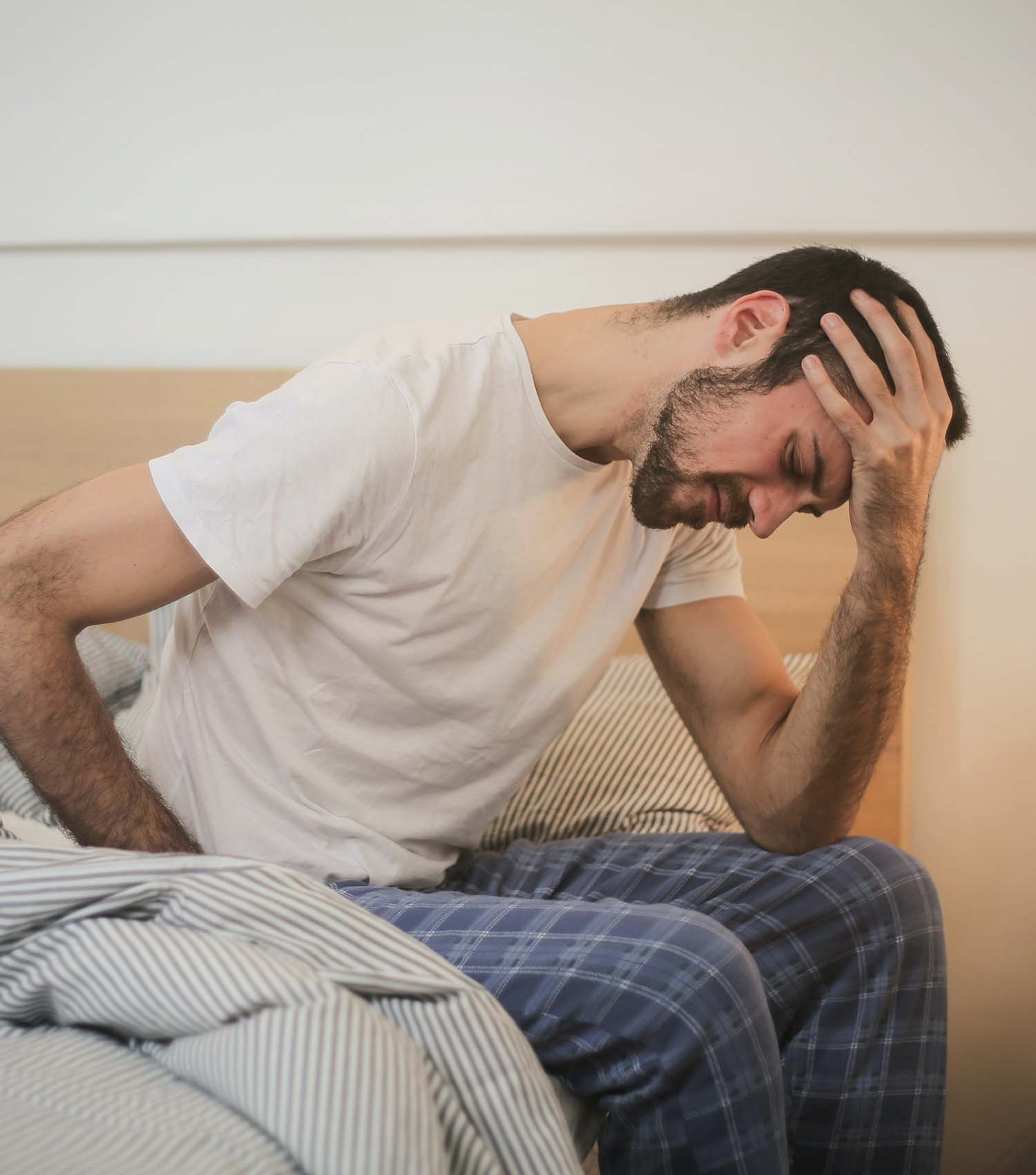 Man sitting on bed waking up with headache
