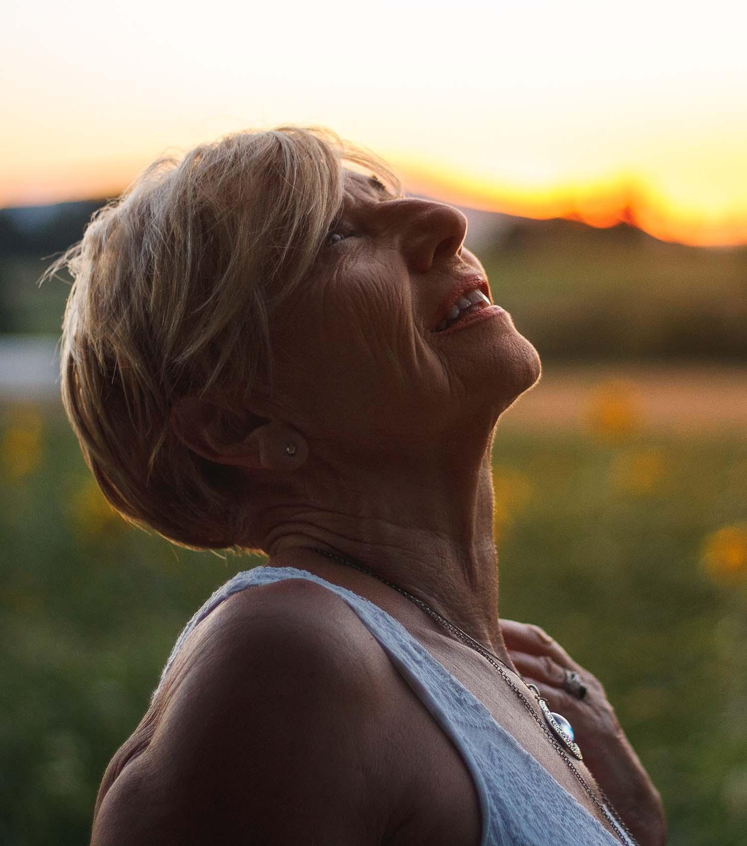 Perimenopausal woman gazing upwards in stillness as sun rises